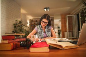 como focar nos estudos: mulher jovem sentada em mesa de casa em volta de vários livros