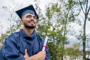 Graduação: homem jovem trajando beca de formatura com seu diploma em mãos