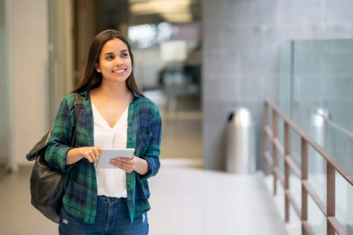 vale a pena fazer uma segunda graduação: jovem mulher em corredor de universidade