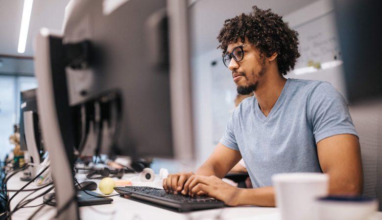 desenvolvedor mobile: homem jovem trabalhando em escritório iluminado em frente ao computador