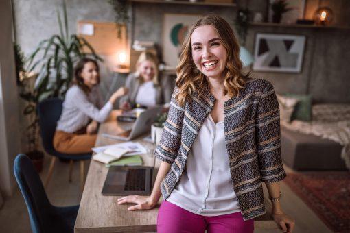 como ser um empreendedor: jovem mulher sorrindo em ambiente de escritório descontraído